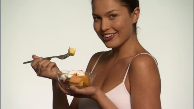 SLO MO, CU, Smiling young woman eating fruits with yogurt in studio, portrait