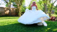 MS Smiling young woman in quinceanera gown twirling in backyard before quinceanera