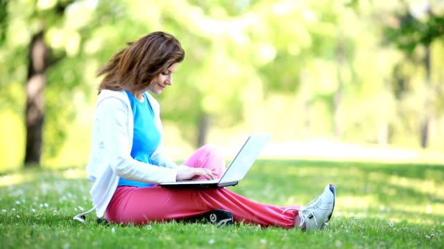 Smilng young woman typing on laptop in the park.