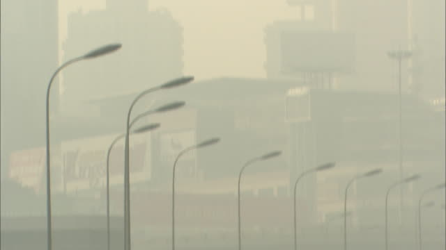 Smog-obscured buildings; tilt down to congested road