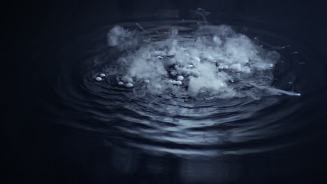 Smoke and bubbles form on the surface of dark water.