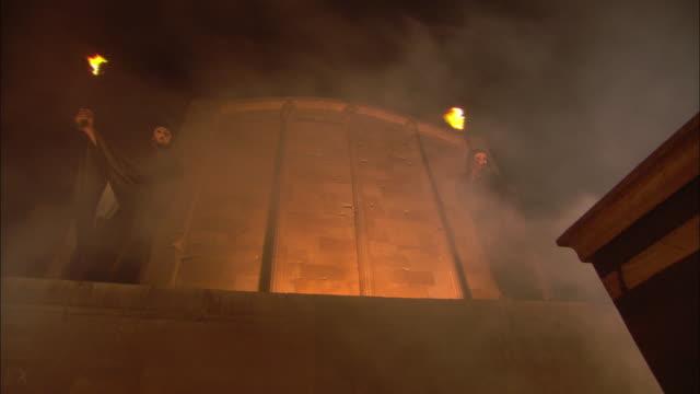 Smoke billows across a temple facade where monks wave flaming torches.