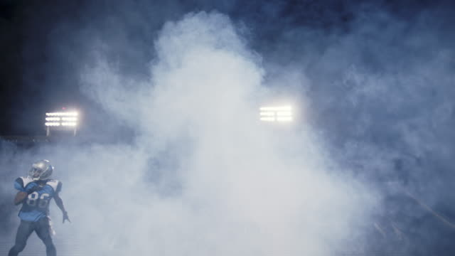 WS SLO MO. Smoke billows under stadium lights as wide receiver leaps into air and catches football.