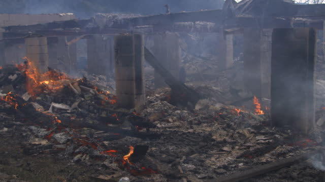 Smoke drifts past smoldering rubble of a house destroyed by fire