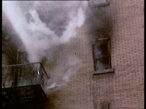 Smoke emerging from windows as water is sprayed across building from fire truck 1970s
