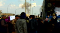 Smoke from an Islamic State car bomb explosion visible in the distance as residents of Mosul queue for food aid