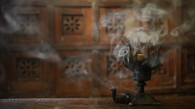 CU Smoke from burning incense sticks in metal holder / Singapore