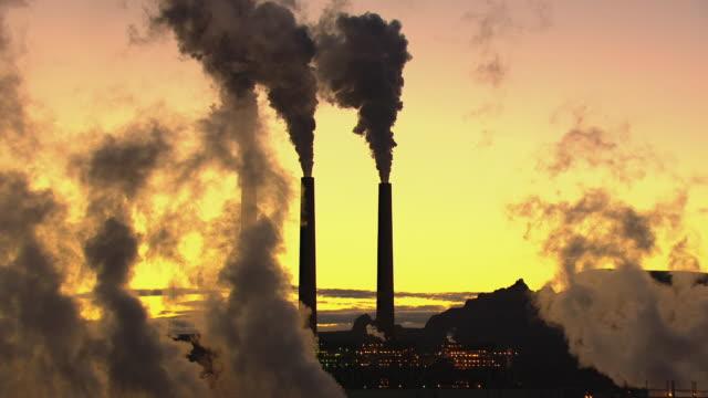 MS AERIAL Smoke rising from Navajo Generating Station against sunrise sky / Arizona, United States