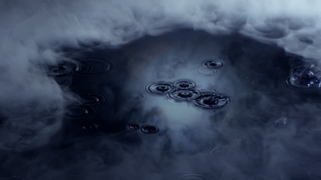 Smoke slowly drifts over a bed of water as water droplets create ripples reflected in a moonlit sky.