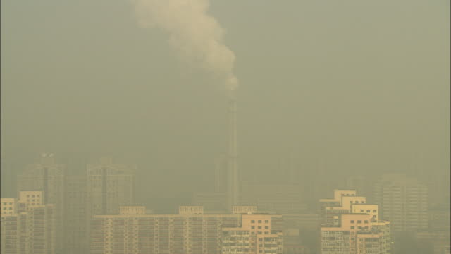 WS HA Smokestack rising high above city and into very smoggy air / Beijing, China