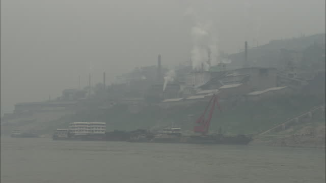 A smokey factory is seen from across a river.