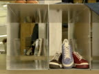 Sneakers on display in shop and feet of customers wearing different styles of trainers London