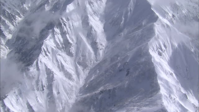 Snow blankets the steep gorges of the Tanigawa Mountain Range in Japan.