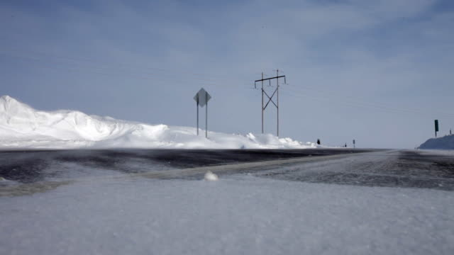 Snow blowing on the road and as a plow approaches
