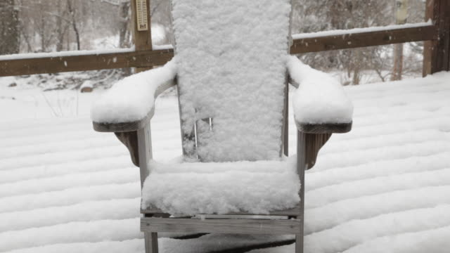 Snow covered Andirondack chair on deck