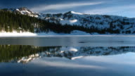 Snow covered mountains mirror in an icy lake as time lapse clouds float in a blue sky.