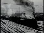 Snow covered railroad yard w/ freight train moving slowly LA WS freight train moving down out of frame smoke engulfing lens WWII