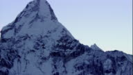 Snow covers a mountain peak in the Himalayas. Available in HD.