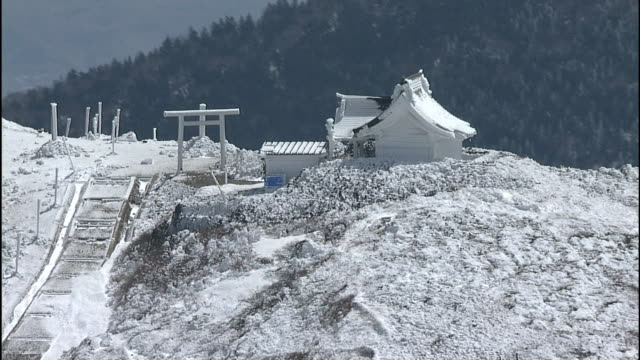 Snow covers the shrine and Torii gate on a summit in the Zao Mountain Range, Japan.