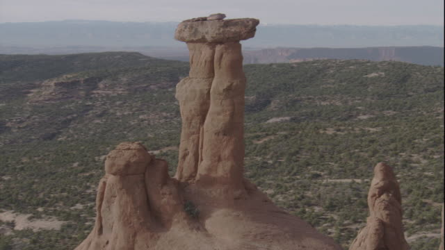 Snow dusts a hammer shaped rock formation and other buttes in a Utah desert. Available in HD.