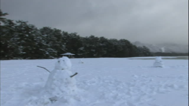 Snow falls over several snowmen in a snowy field on the Amanohashidate sandbar.