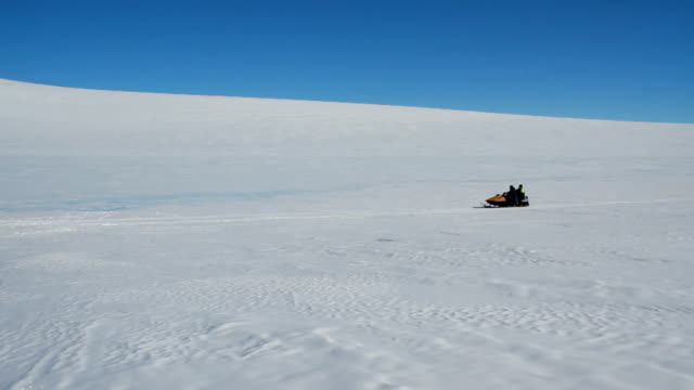 Snow mobile joining a group of scientists SANAE IV is the name of the South African Antarctic research base station It is located in Vesleskarvet...