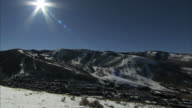 Snow mountains w/ ski trails belong to ski resorts BRIGHT Sun glare top of frame town lower frame UT