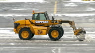 Snow plough clearing snow from runway Orange lights flashing GV Runway area with runway clear of snow BA plane standing at end of runway as starts...