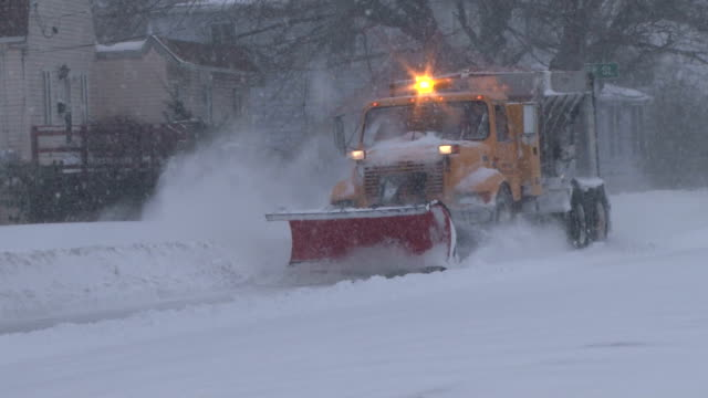 A snow plow barreling through deep snow drifts during the height of a blizzard on Long Island