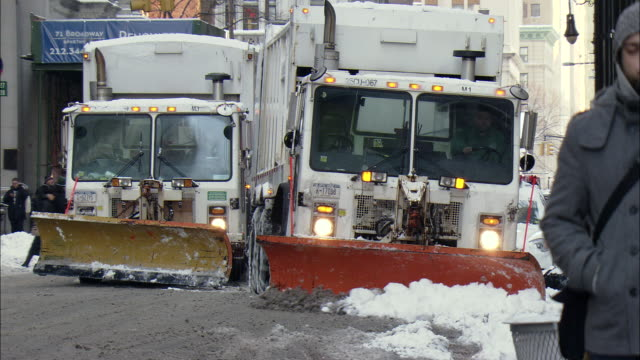 WS ZO PAN TD ZI Snow plow moving on snowy Wall and 3 plows in row / New York, New York, United States