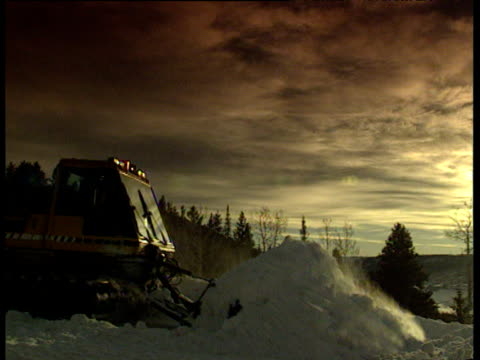 Snow plow pushes snow into pile moving from left to right at dusk then reverses back sunset in background Steamboat Springs Colorado
