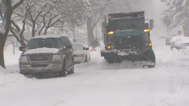 Snow plow trucks plow through snow on road and sprays salt the day after the 5th Largest Blizzard in Chicago history on February 02 2015 in Chicago...