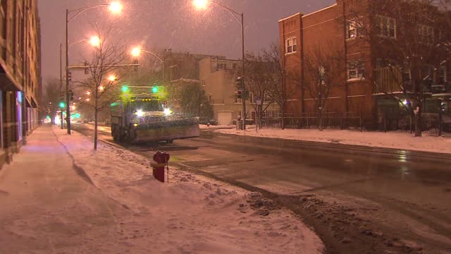 Snow Plows Going Down City Streets At Night on January 02 2014 in Chicago Illinois
