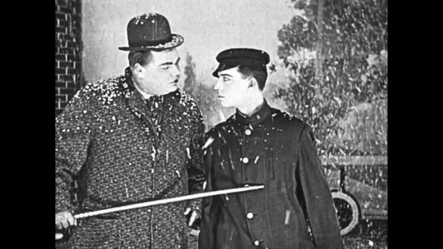 Snow scene on theater stage with Fatty Arbuckle and Buster Keaton driving in wooden cut-out of car