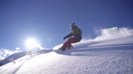 Snowboarder does powder turn