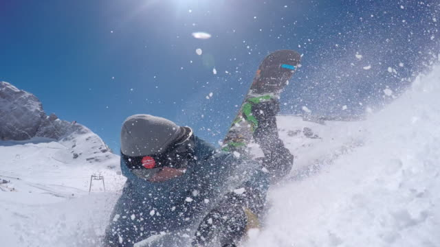 Snowboarder falling while taking a selfie