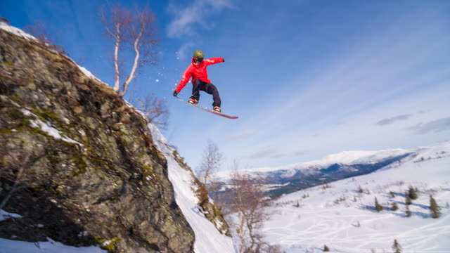Snowboarder jumping off a cliff, landing on freshly fallen snow