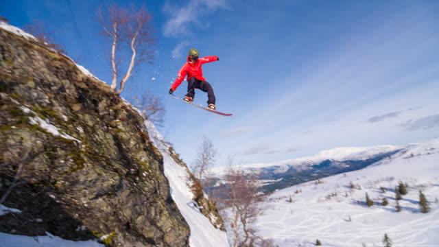 Snowboarder springen van een rots, landing op vers gevallen sneeuw