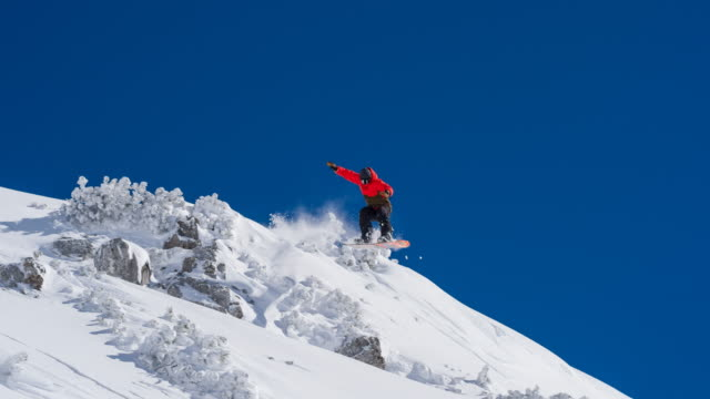 Snowboarder jumping over rocks, riding down the ski slope