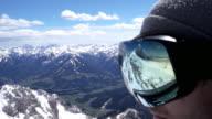 CU  Snowboarder putting on his ski goggles