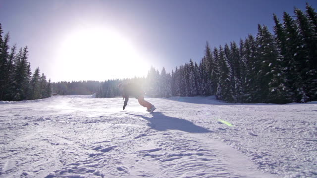 Snowboarder turns on slope