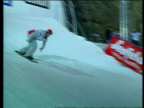 Snowboarder twist jumps out of starting gate and jumps off ramp performing somersault in air whilst holding end of board Seefeld Austria