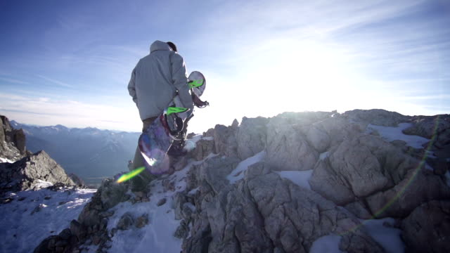 Snowboarder walking up a rocky mountain