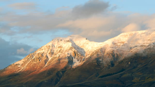 T/L WS Snow-capped Wasatch Mountain range covered with clouds at sunset / Heber, Utah, USA