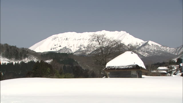 Snow-covered Daisen mountain overlooks houses nestled in the snowy foothills of Tottori Prefecture, Japan.