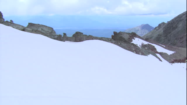 A snow-covered mountain ridge overlooks a lake in Glacier National Park. Available in HD.