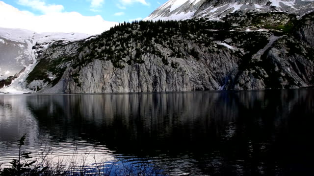 Snowmass Lake Aspen Wilderness Area with Huge Rock Cliffs and amazing Reflection of Alpine Tundra and High Altitude Peaks in Rocky Mountains