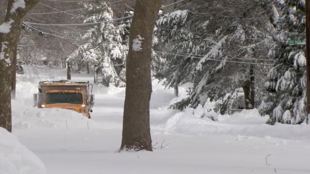 Snowplow passing camera on city street after heavy snowfall