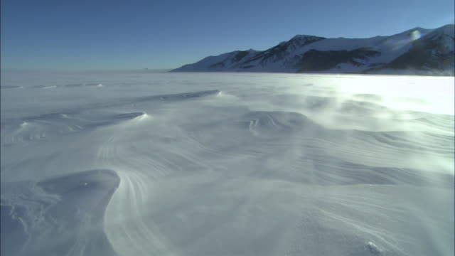 Snowstorm blows over ice sheet ice sculpted by wind