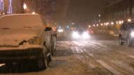 Snowstorm. Winter traffic. Cars on slippery road. Snowfall, snowflakes.
